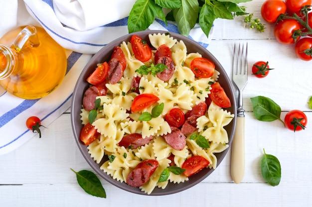 Вкусная паста с колбасками на гриле, свежими помидорами черри и базиликом