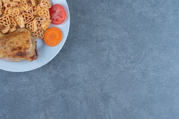 하얀 접시에 고기 조각이 있는 맛있는 파스타.
