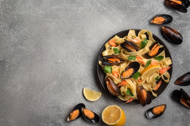 Tasty pasta with mussels, squid, parsley and lemon, top view.