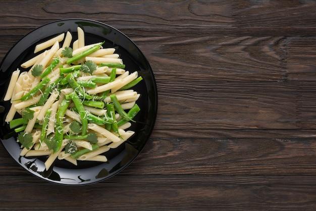黒い平板にパルメザンチーズと緑のさやのおいしいパスタ。健康食品。