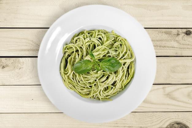 Tasty pasta with  pesto sauce on background