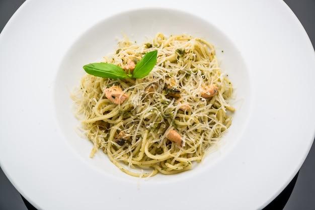 Вкусная паста с лососем, шпинатом на тарелке