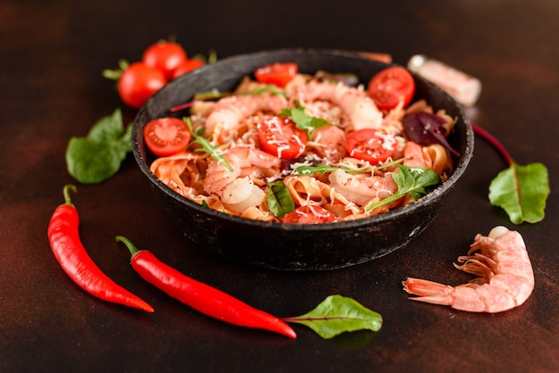 Tasty pasta with shrimp and tomato on a frying pan