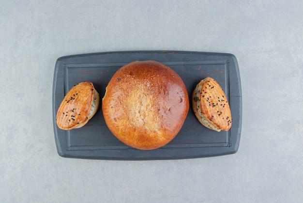 ブラックボードにチーズとパンが入ったおいしいペストリー。