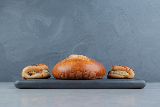 Tasty pastries with cheese and bun on black board.
