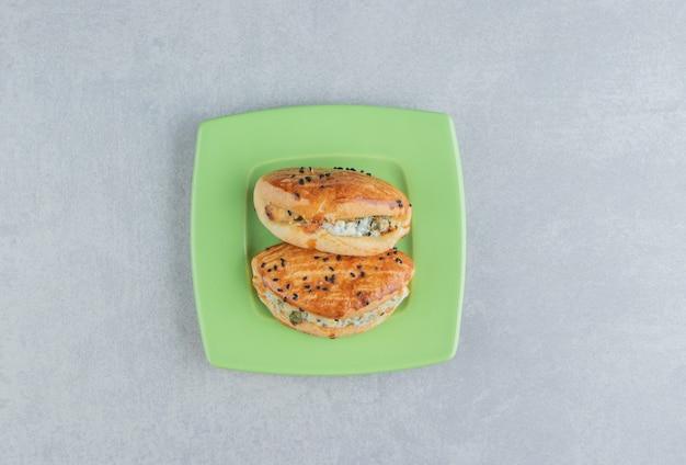 緑のプレートにチーズが入ったおいしいペストリー。