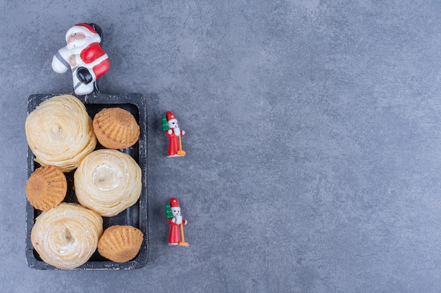 灰色の表面にクリスマスのおもちゃが付いたおいしいペストリー
