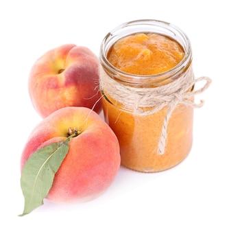 白で隔離された新鮮な桃とおいしい桃ジャム