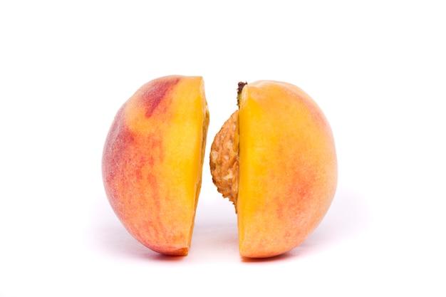 Tasty peach sliced on half on white
