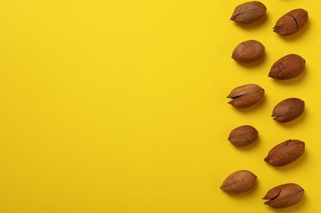 Вкусные орехи пекан на желтой стене, место для текста и вид сверху