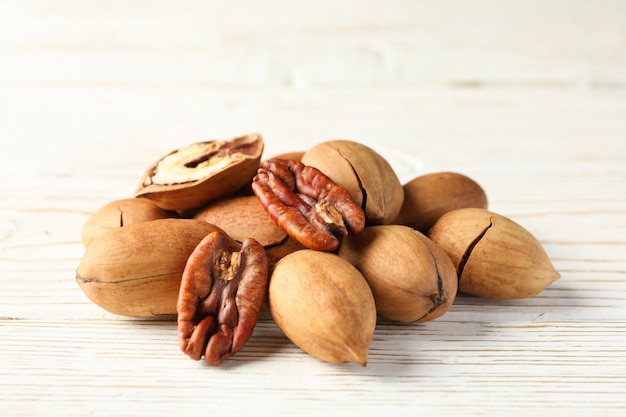 Tasty pecan nuts on white wooden table