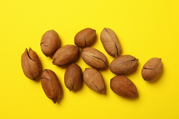 Tasty pecan nuts on yellow, top view