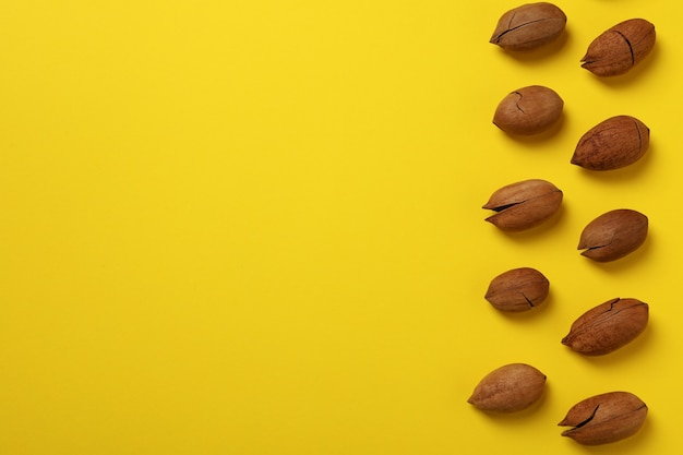 Tasty pecan nuts on yellow wall, space for text and top view