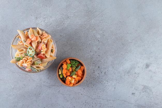 Вкусные макароны пенне и свежий салат на каменном фоне.