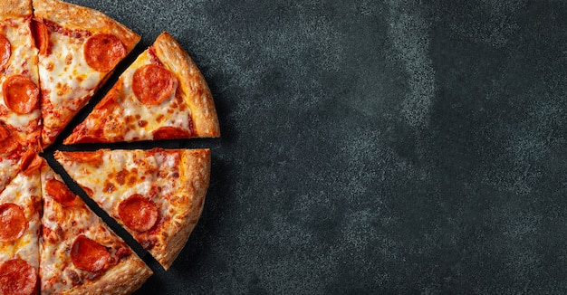 Tasty pepperoni pizza on a black concrete background.