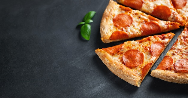 Tasty pepperoni pizza on black concrete background
