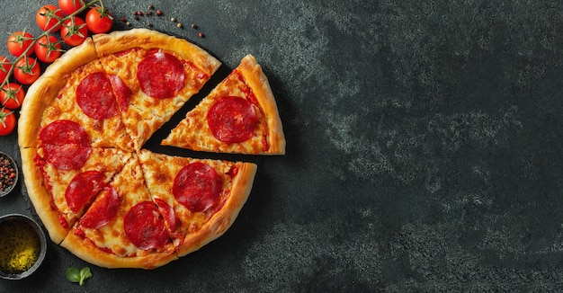 Tasty pepperoni pizza and cooking ingredients.