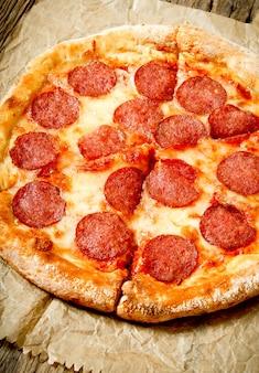 古い紙においしいペパロニピザ。木製の背景に。