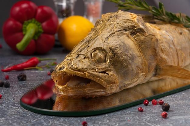 야채와 향신료로 장식 된 거울에 구운 맛있는 농어를 닫습니다.