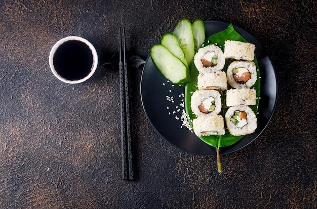 어두운 테이블에 간장, 생강, 와사비, 젓가락으로 검은 접시에 참깨에 연어와 크림 치즈가 들어간 맛있는 필라델피아 롤 초밥. 스시 메뉴. 배달 서비스 일본 아시아 음식.