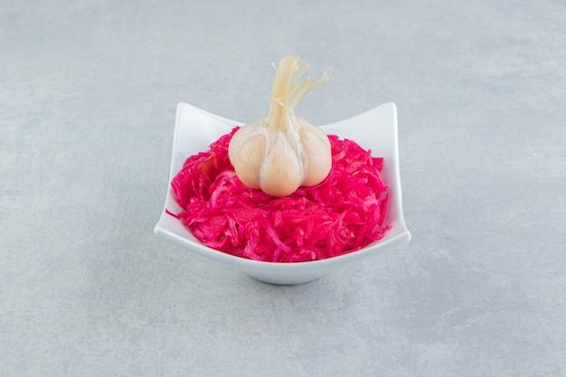 하얀 그릇에 마늘을 곁들인 맛있는 절인 양배추.