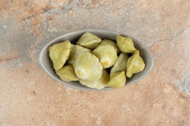 Gustosi frutti sottaceto in ciotola grigia