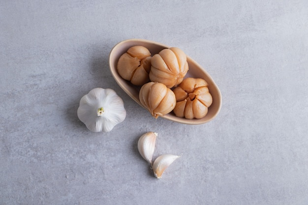 Tasty pickled garlic in the bowl placed on stone table.