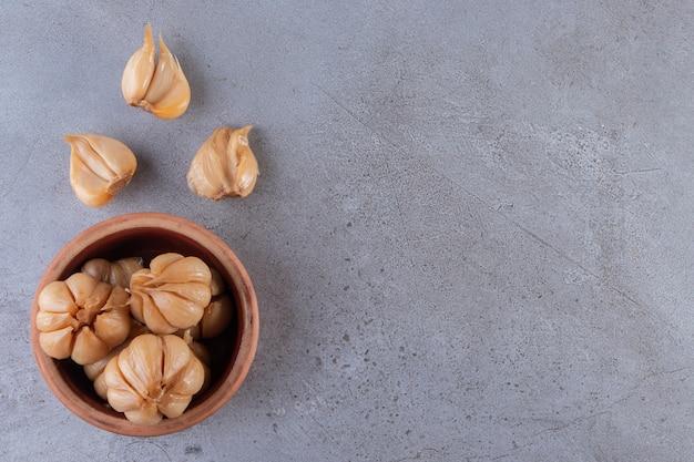 Вкусный маринованный чеснок в миске на каменном столе.
