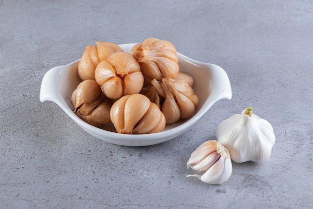 Tasty pickled garlic placed on a stone surface.