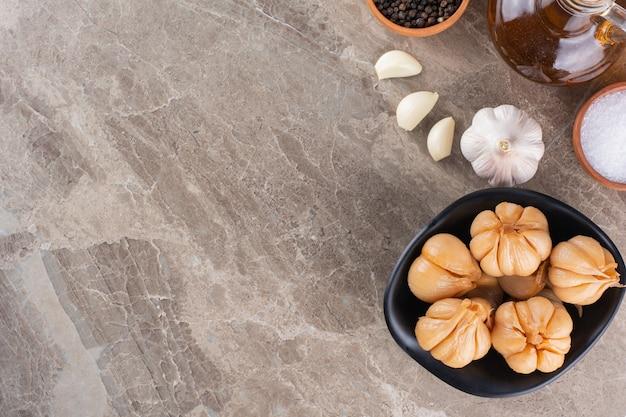石のテーブルにコショウのとうもろこしを乗せたおいしいにんにくのピクルス。