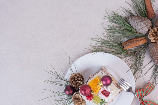 Tasty piece of cake with pinecones and branch of tree