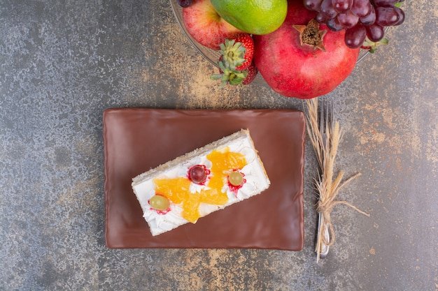 A tasty piece of cake with various fruits on marble space.