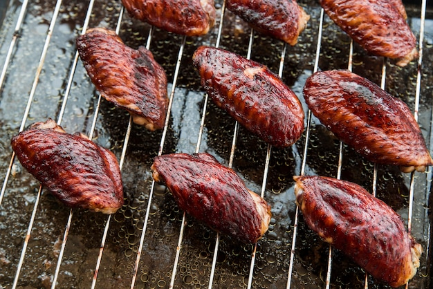 Tasty pieces of chicken meat on metal grill
