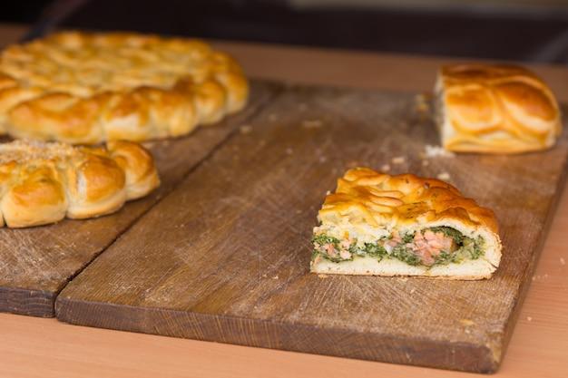 ゲストに提供するために必要に応じてスライスされているケータリングイベントで木製のまな板の上においしい肉と野菜で満たされた新鮮な無愛想なペストリーとおいしいパイ