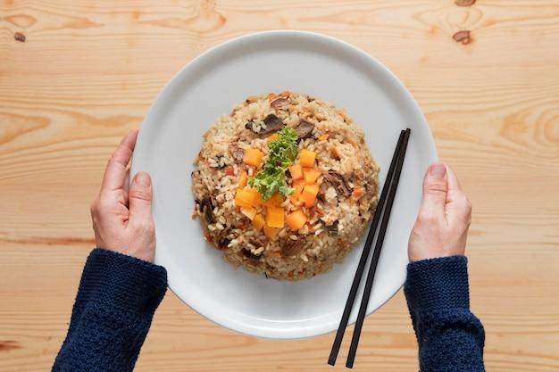 Tasty pilaf dish and chopsticks