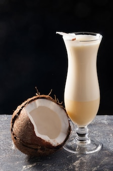 Tasty pina colada coconut cocktail on a black background