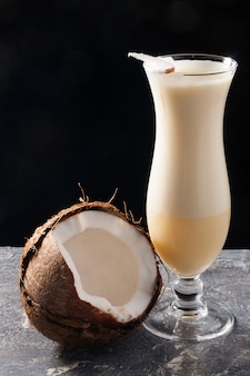 Tasty pina colada decorated with coconut on a black background
