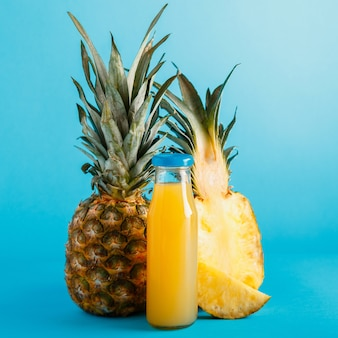 Tasty pineapple juice in glass bottle with ingredients on blue color summer background. fresh natural pineapple cocktail, pineapple juice in glass bottle. square. high quality stock photo.
