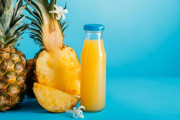 青い色の夏の背景のコピースペースに材料の花とガラス瓶のおいしいパイナップルジュース。新鮮な天然パイナップルドリンク、ボトルに入ったパイナップルジュース。高品質のストックフォト。