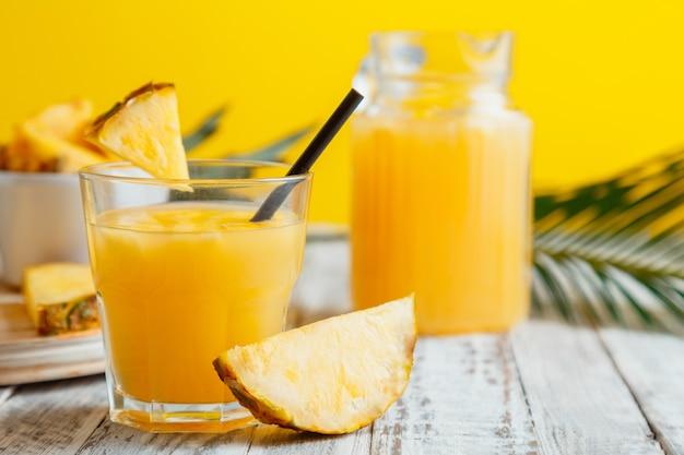 재료와 유리에 맛 있는 파인애플 주스. 노란색 여름 배경 야자잎이 있는 흰색 나무 테이블에 있는 유리 저그에 있는 신선한 천연 파인애플 주스 칵테일과 파인애플 주스.