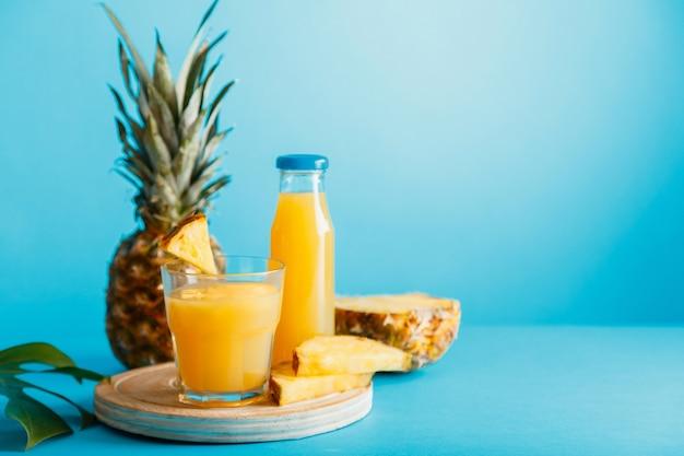 材料とガラスのおいしいパイナップルジュース、青い色の夏の背景にガラスジュースボトル。新鮮な天然パイナップルカクテルとパイナップルジュースをグラスに入れ、コピースペース付きのボトルに入れます。