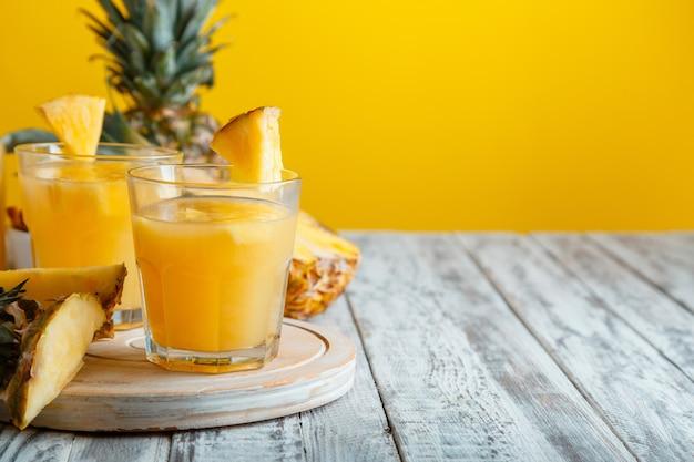 黄色の夏の背景を持つ白い木製のテーブルの材料とガラスのおいしいパイナップルジュース。新鮮な天然パイナップルジュースカクテルとコピースペース付きジュースグラス。高品質のストックフォト。