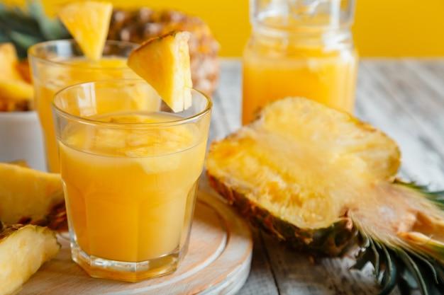パイナップルフルーツスライスとガラスのおいしいパイナップルジュース。白い木製のテーブルの上のガラスの新鮮な天然パイナップルカクテルとジュース。高品質のストックフォト。