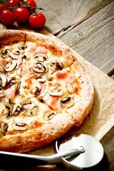 맛있는 피자와 오래 된 종이에 칼. 나무 배경.