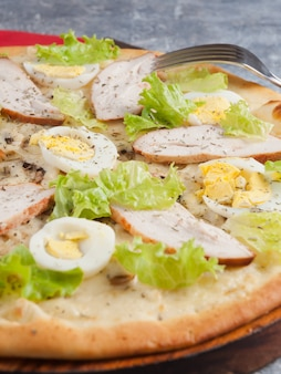 Tasty pizza caesar close-up of the selected focus