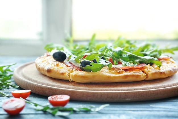 青い木製のテーブルにおいしいピザチェリートマト、オリーブ、ルッコラ