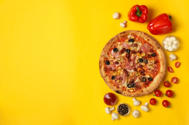 Tasty pizza and ingredients on yellow
