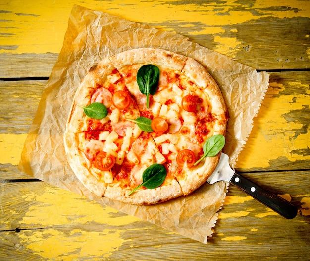 오래 된 종이에 맛있는 피자. 나무 배경.