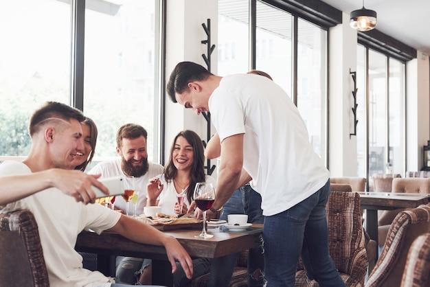 술집에서 쉬고 젊은 웃는 사람들의 그룹과 함께 테이블에 맛있는 피자.