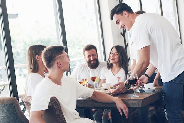 パブで休んでいる若い笑顔の人々のグループと一緒に、テーブルの上においしいピザ。